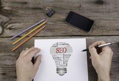 Nuvola di parola della lampadina di SEO (ottimizzazione del motore di ricerca) Immagine Stock