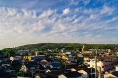 Nuvola e cielo blu bianchi oltre le case Immagine Stock