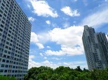 Nuvola lanuginosa bianca che galleggia su Sunny Sky blu vibrante fra le alte costruzioni Immagine Stock