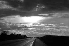 Nuvola nera bianca sopra una strada Immagini Stock