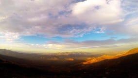 Nuvole al rallentatore e Sun che mettono Timelapse sopra le montagne Fotografia Stock Libera da Diritti