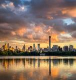 Nuvole al tramonto, grattacieli di Manhattan attraverso il Central Park Immagine Stock