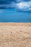 Nuvole alte e di pioggia vicine della spiaggia di sabbia e Shelly Fotografia Stock