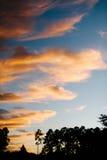 Nuvole arancio di caduta contro un cielo blu. Immagine Stock Libera da Diritti