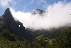 Nuvole attraverso le montagne Fotografia Stock
