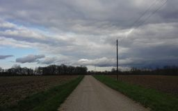Nuvole basse che sembrano giù la strada campestre orientale immagini stock libere da diritti