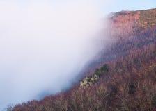 Nuvole basse muoventesi che sorpassano la collina immagine stock