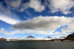 Nuvole bianche gonfie, cielo blu, picchi di montagna e ghiacciai nelle Svalbard artiche Fotografia Stock