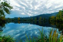 Nuvole che riflettono in un lago Immagini Stock Libere da Diritti
