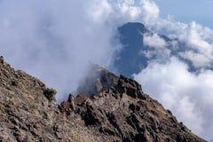 Nuvole che si formano sopra le montagne e la cresta vulcanica a Roque de los Muchachos su La Palma, isole Canarie immagini stock