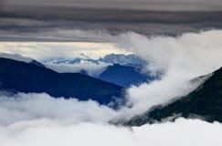 Nuvole che turbinano intorno e sopra Carnic e Julian Alps Fotografia Stock