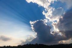 Nuvole in cielo blu su alba del fondo e sui raggi di Sun Fotografie Stock