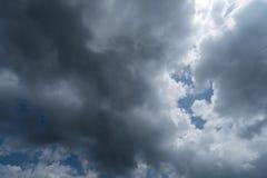 Nuvole con fondo, luce solare attraverso il fondo molto scuro delle nuvole delle nuvole di tempesta scure Immagini Stock Libere da Diritti