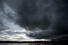 Nuvole con fondo, luce solare attraverso il fondo molto scuro delle nuvole della nuvola di tempesta scura immagine stock