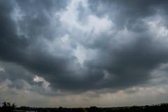 Nuvole con fondo, luce solare attraverso il fondo molto scuro delle nuvole della nuvola di tempesta scura Fotografia Stock