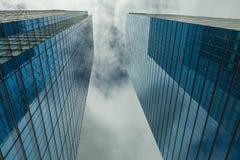 Nuvole delle incisioni dei grattacieli nel cielo blu immagine stock
