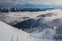 Nuvole di Ski Lift Riding Up Through alla località di soggiorno Immagini Stock