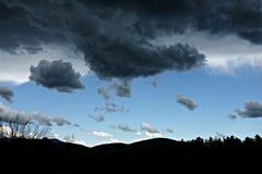 Nuvole di tempesta del nero della siluetta della montagna Fotografia Stock