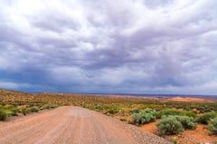 Nuvole di tempesta e strada della ghiaia nell'Utah del sud fotografie stock libere da diritti