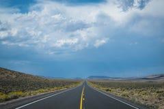 Nuvole di tempesta scure sopra la strada principale del deserto fotografie stock libere da diritti