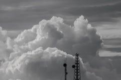 Nuvole e cielo in bianco e nero con la cima dell'antenna Fotografia Stock