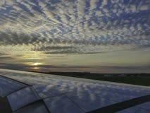 Nuvole e cielo blu che riflettono sull'ala dell'aeroplano al tramonto fotografia stock libera da diritti