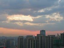 Nuvole e cielo drammatici sopra la città al tramonto fotografie stock