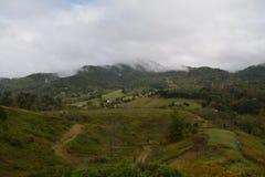 Nuvole e Sun sopra il paesaggio delle montagne immagini stock libere da diritti