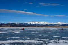 Nuvole esili che guardano dall'alto in basso i pescatori del ghiaccio Fotografie Stock