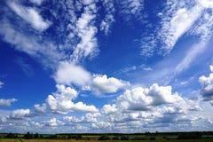 Nuvole gonfie bianche in cielo blu, paesaggio agricolo Immagini Stock