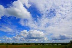 Nuvole gonfie bianche in cielo blu, paesaggio agricolo Fotografia Stock