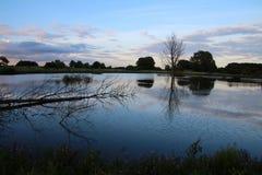 Nuvole grige che riflettono nel lago del prato Fotografia Stock