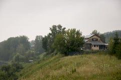Nuvole grige pesanti nel cielo freddo di autunno sopra il villaggio con le casette lontano nelle montagne e nei campi Viaggiando  Immagini Stock