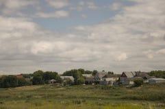 Nuvole grige pesanti nel cielo freddo di autunno sopra il villaggio con le casette lontano nelle montagne e nei campi Viaggiando  Fotografie Stock
