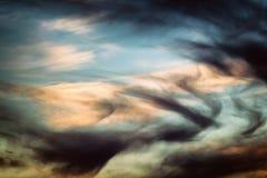 Nuvole leggere sul contrasto con il buio Immagine Stock