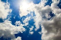 Nuvole luminose con cielo blu, raggi del sole Fotografie Stock Libere da Diritti