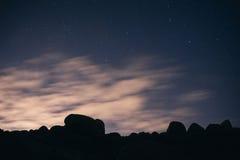 Nuvole nel moto contro il cielo stellato di notte Immagini Stock