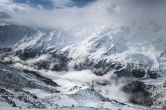 Nuvole nelle alpi nevose Fotografie Stock