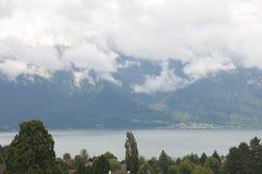 Nuvole scure che galleggiano sopra le montagne fotografia stock