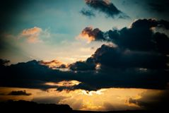 Nuvole scure contro il cielo uguagliante ed i raggi del sole immagine stock libera da diritti