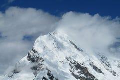 Nuvole sul picco della neve dell'alta montagna Fotografia Stock