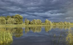 Nuvole temporalesche sopra un bello lago fotografie stock libere da diritti