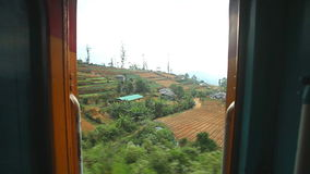 NUWARA ELIYA, SRI LANKA - MARCH 2014: View of the Nuwara Eliya countryside from the moving train. The Sri Lankan railway transport. S millions of people daily in stock footage