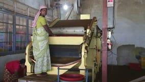NUWARA ELIYA, SRI LANKA - MARCH 2014: View of a two local women working on a machine in the tea factory in Nuwara Eliya. Sri Lanka stock video footage