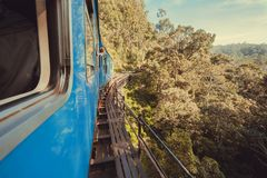 Travelers in train riding over the bridge over the cliff Stock Photos