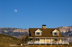 Nuwest ranch. Modern ranch style home with warparound porch, full moon rising in mountain setting Royalty Free Stock Photo