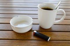 Nwhite keramisk kopp med ett uppfriskande varmt kaffe för morgon med cigaretten för svart för askfat för skinande tesked för tedr royaltyfri bild