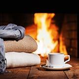NWhitekop thee en warme wollen dingen dichtbij open haard royalty-vrije stock afbeeldingen