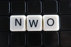 NWO text word crossword. Alphabet letter blocks game texture background. Black background. Royalty Free Stock Photography