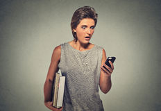 Nxious looking young woman starring at cell phone seeing bad news or photos Stock Image